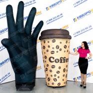 огромная рекламная рука и стаканчик с кофе